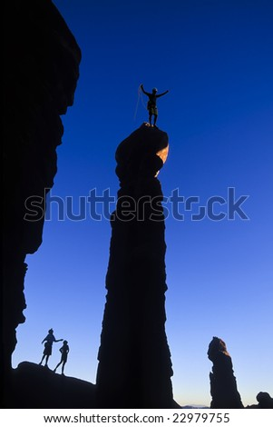 A climber celebrates on the summit of a rock pinnacle in Canyonlands National Park, Utah. - stock photo