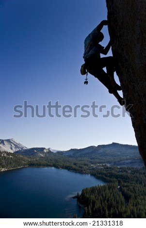 A climber clings to a rock face high above Lake Tenaya in Yosemite National Park, California, on a summer day. - stock photo