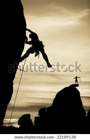A climber clings to the side of an overhanging cliff in The Sierra Nevada Mountains, California. - stock photo