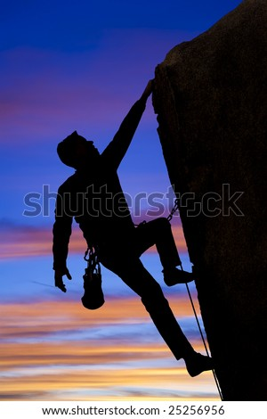 A climber clings to the side of an overhanging rock spire in The Sierra Nevada Mountains, California. - stock photo