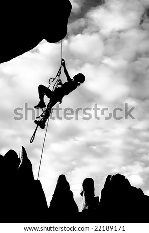 A climber dangles in midair as she rappells from the summit of a rock spire in The Sierra Nevada Mountains, California. - stock photo