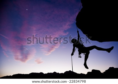 A climber dangles in midair as she rappels from the summit of a rock spire after a successful ascent in The Sierra Nevada Mountains, California. - stock photo
