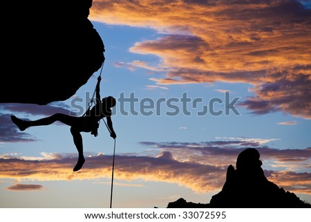 A climber dangles in midair as she rappels from the summit of a rock spire after a successful ascent in The Sierra Nevada Mountains, California.