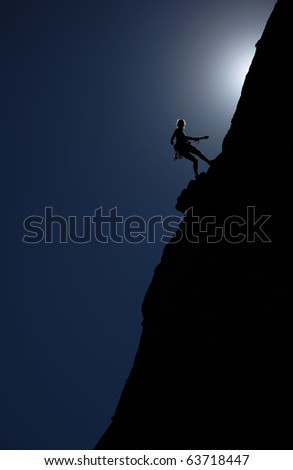 A climber hangs from a rope on the edge of a steep cliff in the late afternoon sun.
