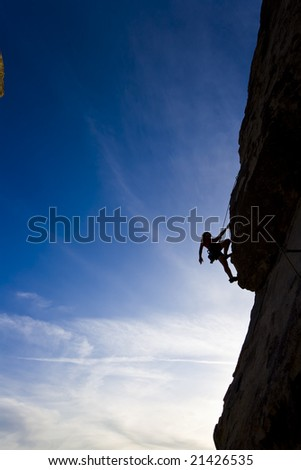 A climber is silhouetted against the evening sky as she clings to a steep rock face in Joshua Tree National Park, California. - stock photo