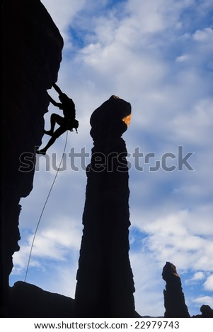 A climber is silhouetted as he clings to the side of an overhanging rock spire in Canyonlands National Park, Utah.