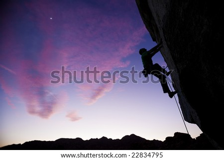 A climber is silhouetted as he makes his way up an overhanging, sheer, rock face in The Sierra Nevada Mountains, California.