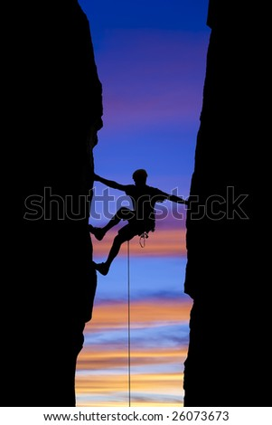 A climber is silhouetted as he reaches across a gap in the rock, in the Sierra Nevada  Mountains, California. - stock photo