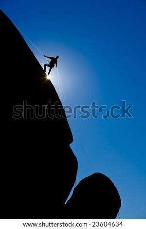 A climber is silhouetted as rappels down a steep rock face in the Sierra Nevada Mountains, California. - stock photo