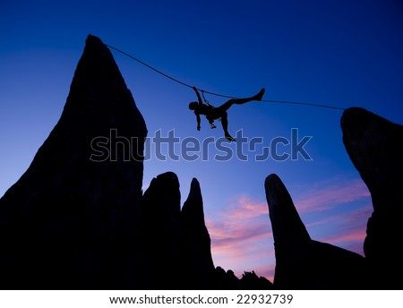 A climber is silhouetted as she pulls herself across a gap between two pinnacles, in the Sierra Nevada  Mountains, California. - stock photo