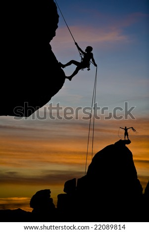 A climber is silhouetted as she rappels from the summit of a rock spire in The Sierra Nevada Mountains, California, after a successful ascent. - stock photo