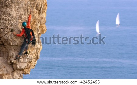 A climber on a rocky wall with two boat with sails racing in the sea below - stock photo