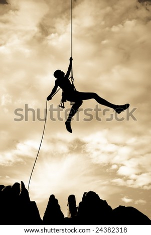 A climber rappelling from the summit of a rock spire after a successful ascent in The Sierra Nevada Mountains, California. - stock photo