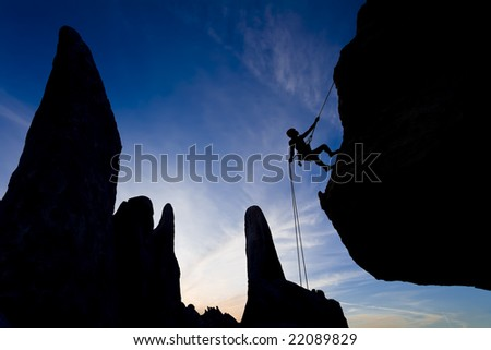 A climber rappelling from the summit of a rock spire is silhouetted against the evening sky, in The Sierra Nevada Mountains, California. - stock photo