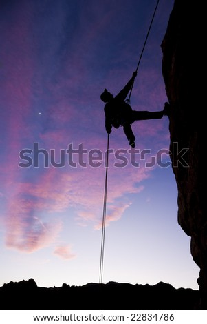 A climber rappels down from the summit of a rock outcrop after a successful ascent in The Sierra Nevada Mountains, California.