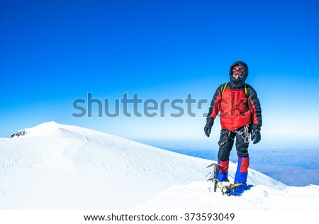 A climber reaching the summit of the mountain - stock photo