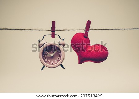 A clock and a red heart hung together on a rope / time and love concept - stock photo