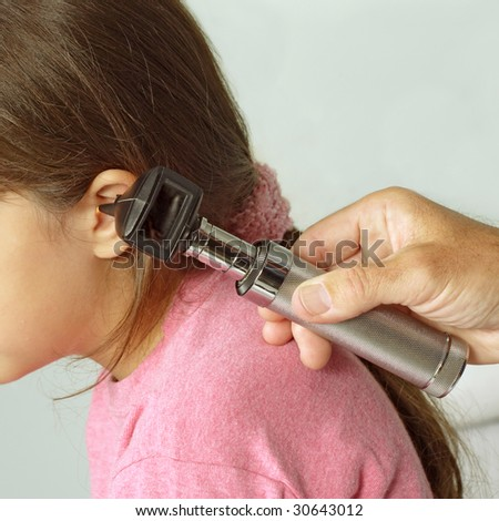A close-cropped image of a doctor examining the ear of a young girl with a otoscope. - stock photo