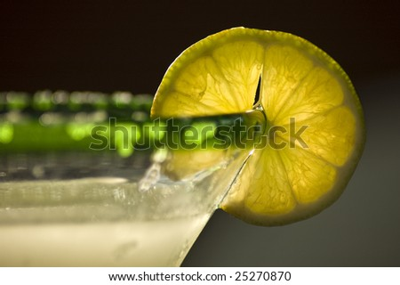 A close photograph of a margarita with a lemon slice. - stock photo