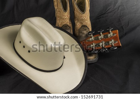 A close shot of a pair of boots. cowboy hat and a guitar handle. - stock photo