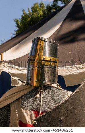 A close shot of a person who dresses up historically to mimic a knights templar in full armour holding a shield. - stock photo