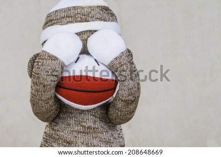 A close shot of a sock monkey playing peek-a-boo with their hand covering its eyes. - stock photo
