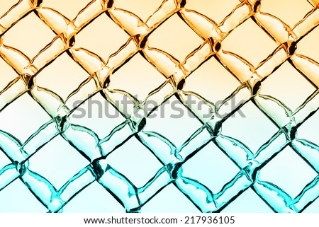 A close up abstract background image of a chain link fence.  The diamond pattern is covered in an ice texture and the image is toned in hues of warm orange fading into cool light blue colors.   - stock photo