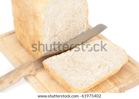 A close up angled studio view of a loaf of homemade bread and a slice on a wooden breadboard with a bread knife.