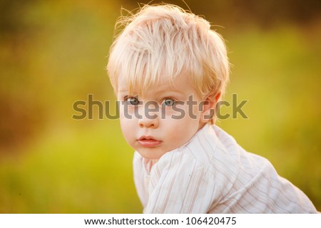 A close-up cute little blonde 1 year old boy outdoors against a blurred green background.  His big blue eyes are looking at the camera.