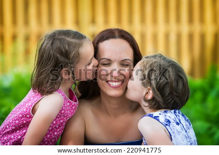 A close up family picture of two daughters on either side of their mother each giving a kiss on her cheek.  - stock photo