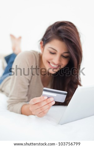 A close up focus shot on the credit card that the smiling woman is holding as she uses her tablet. - stock photo