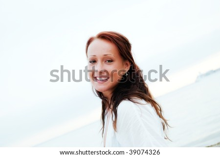 A close up glamorous portrait of a young woman smiling on a beach