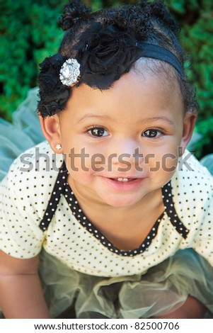 A close-up head shot of an eleven month old female baby in a polka dot tutu. - stock photo