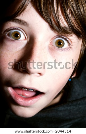 A close-up headshot of a wide-eyed boy. - stock photo