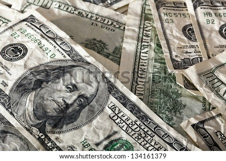 A close up high angle view of a very large amount of crumpled 100 US$ money notes in a bulky mess, with warm & contrasty lighting. - stock photo