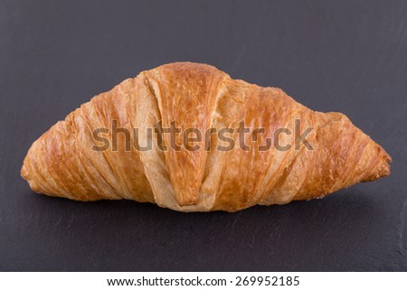 A Close up Image of a Croissant on a Slate Board.  - stock photo