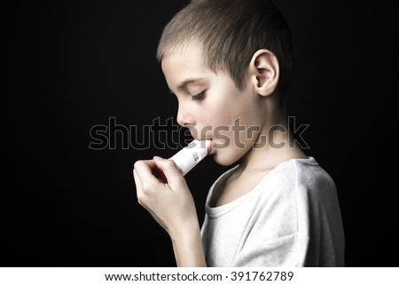 A Close up image of a cute little boy using inhaler for asthma.  - stock photo