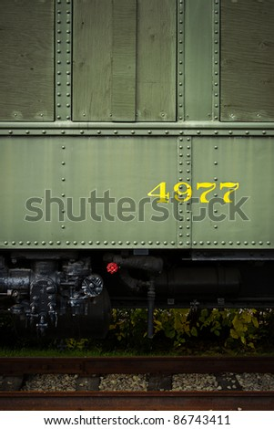 A close-up image of a section of a green, antique train-car that has been boarded-up with the number 4977 printed on its side. - stock photo