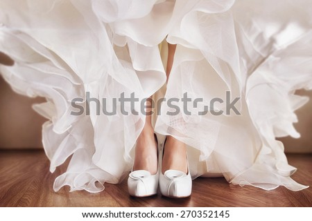 A close up image of elegant floor-length wedding dress. Concept of bride morning. - stock photo
