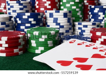 A close up image of stacked poker chips and a royal flush.