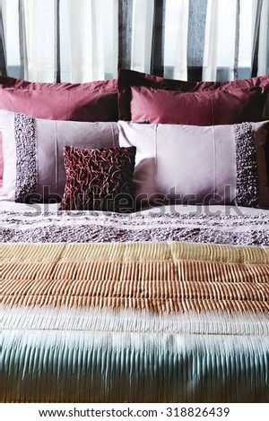 a close up in a bed in a studio photo with beautiful pillows and blanket with beautiful and  shadows - stock photo