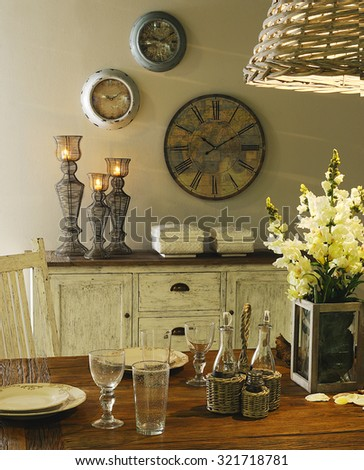 a close up in a table with dinnerware set and with a buffet on background with candles and clocks on the wall