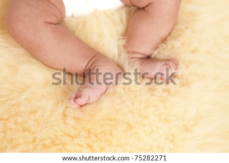 A close up of a baby feet, while laying down.