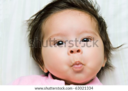 A close-up of a baby girl making a kiss face