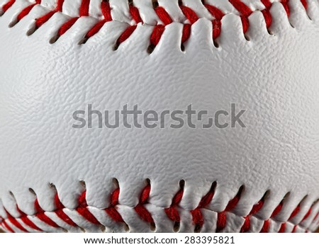 A close up of a baseball showing the texture of the leather. - stock photo