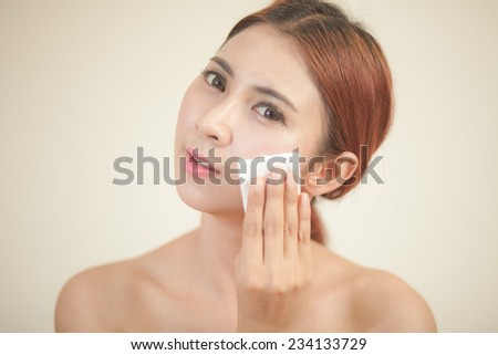 A close up of a beautiful young woman removing her make up. - stock photo
