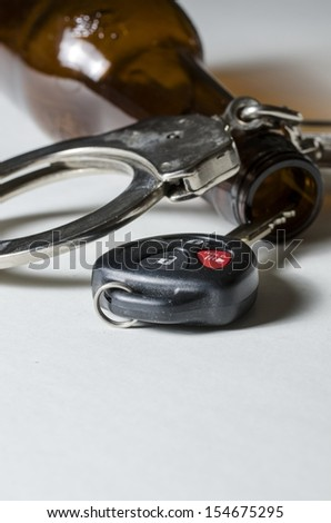 A close up of a beer bottle with car key and handcuffs. - stock photo