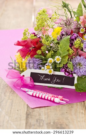 "a close up of a bouquet of flowers with a black label saying: ""Thank you!"" on magenta paper"