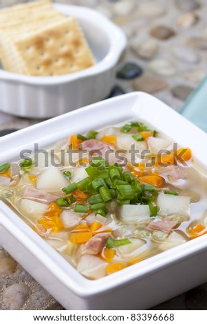 A close up of a bowl of homemade soup with crackers.