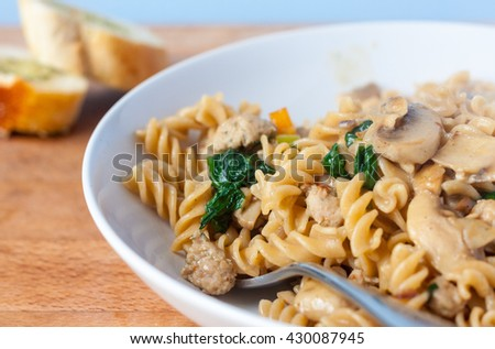 A close-up of a bowl of sausage, mushroom and spinach pasta using wholewheat fusilli